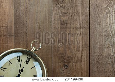 Vintage clock on a wood background. Part of clock showing. Time almost 12 o'clock. Vintage traditional muted warm brown colors. Lots of copy