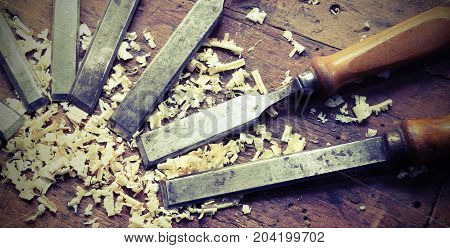many sharp chisels with sawdust and vintage effect poster
