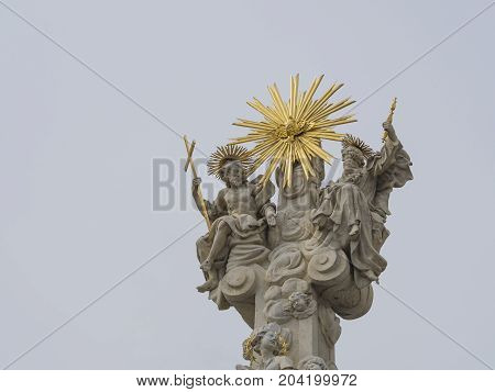 top of baroque plague column monument with saint peter and saint paul and golden sun in Olomouc city on light sky background