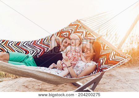 Happy Stylish Family Playing With Cute Daughter, Relaxing In Hammock On Summer Vacation In Evening S
