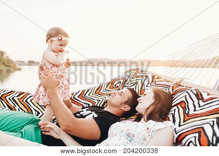 Happy Stylish Family Relaxing In Hammock On Summer Vacation In Evening Sun Light On The Beach. Hipst