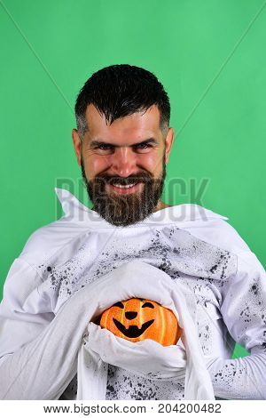 Man with evil smile isolated on green background. Halloween character in white long sleeved ghost costume. Guy with beard holds orange pumpkin with smile. October time and spooky holiday concept