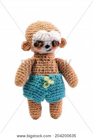 Brown knitted monkey isolated on white background. A handmade toy on a white background.