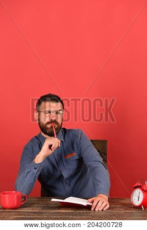Man With Thoughtful Face Sits At Wooden Table