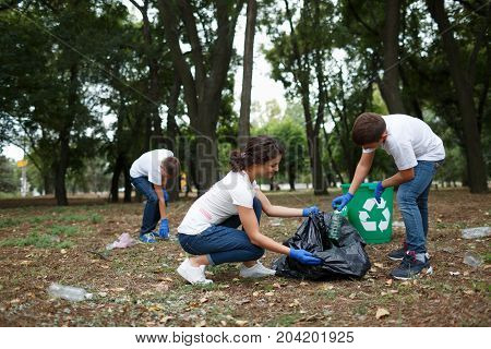 Image of young volunteers and children collecting garbage in park. Bin in park. Ecology group. Concept of environmental protection. Team with recycle project outside.