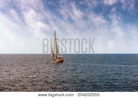 One sailing boat in the open sea.