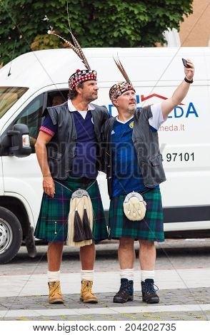 VILNIUS LITHUANIA - SEPTEMBER 1 2017: Two middle age men Scotland football team fans in national clothes taking a selfie on the street in Vilnius Lithuania