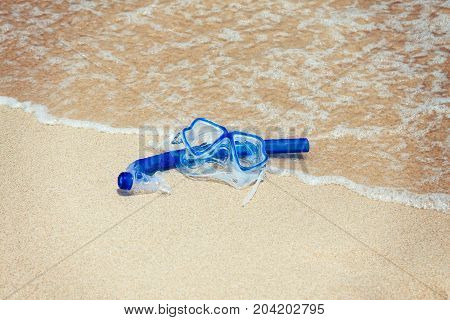 Snorkel mask on the beach sand at summer