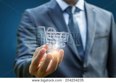Businessman Shows A Shopping Cart With Gears.