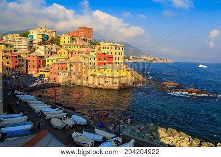 06.08. 2017. Boccadasse Italy district of city Genoa ( Genova ) old fishing village in the sunset sun. Colorful ancient houses on the beach. Embankment with fishing boats. People on small stone beach. Ligurian Riviera. Hot summer 2017 - season beach vacat