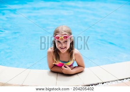 Child With Goggles In Swimming Pool. Kids Swim.
