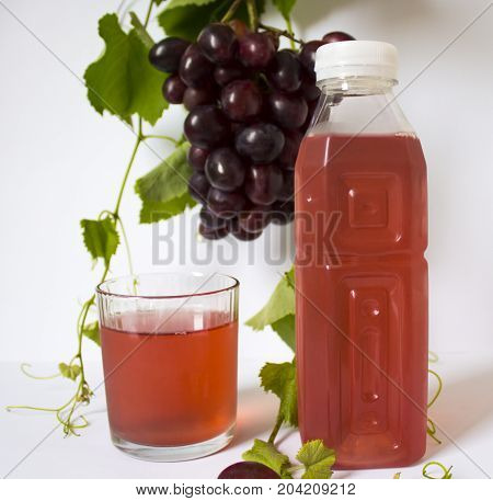 grapes on a white background. a bunch of grapes. grapes, green leaves. dark blue grapes. bottle of juice