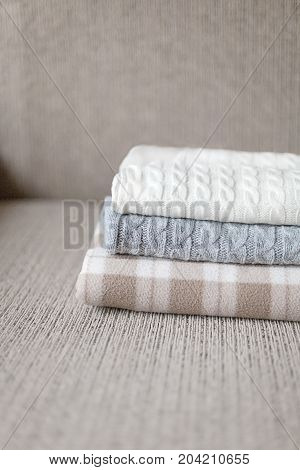 Woolen plaids or sweaters on a grey sofa, winter or autumn season.
