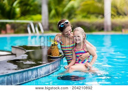 Mother And Child Drink Juice In Swimming Pool