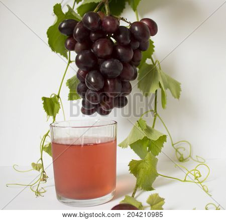 grapes on a white background. a bunch of grapes. glass with juice. grapes, green leaves. dark blue grapes