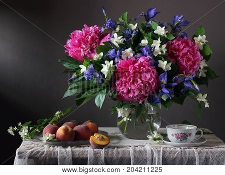 Bouquet of peonies irises and Jasmine in the jar and peaches on a table with lace tablecloth. Still life with a bouquet of beautiful cultivated flowers fruits and retro Cup.