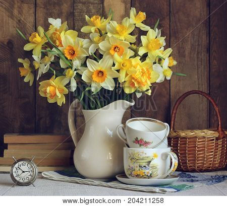 Bouquet of yellow daffodils in a white jug. Still life in rustic style with flowers alarm clock and kitchenware.