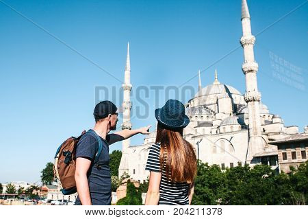 A couple of tourists a young man and a pretty woman stand next to the world-famous Blue Mosque also called Sultanahmet in Istanbul, Turkey.