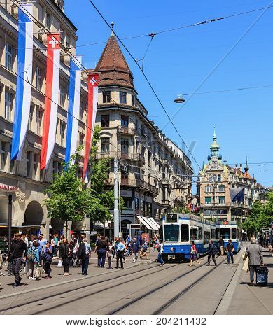 Zurich, Switzerland - 26 May, 2016: people and trams on Bahnhofstrasse street. Bahnhofstrasse is Zurich's main downtown street and one of the world's most expensive and exclusive shopping avenues.
