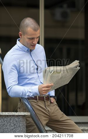 Young Businessman Standing And Read  Newspapers