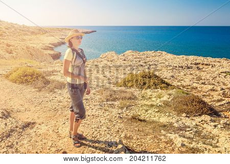 Young woman tourist in seascape picturesque view of Mediterranean Sea Cyprus Ayia Napa Cape Greco peninsula Kavo Greco national forest park
