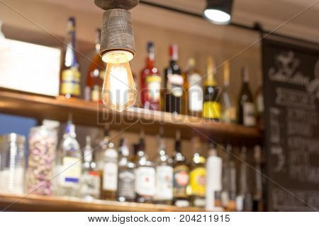 Alcoholic bottles on the bar rack in the blur. The light is in focus.