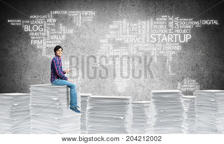 Young man in casual wear sitting on pile of documents with business-related terms in form of world map on background. Mixed media.