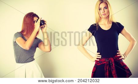 Photographer and model. Mulatto girl shooting images taking photos with camera photographing blonde woman