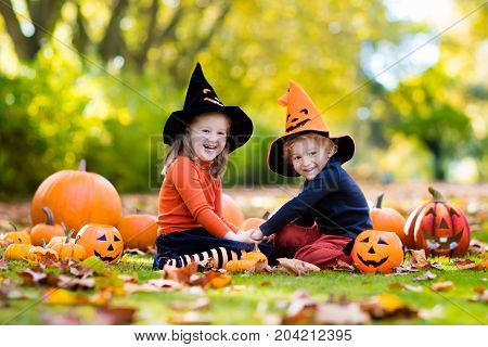 Kids With Pumpkins In Halloween Costumes