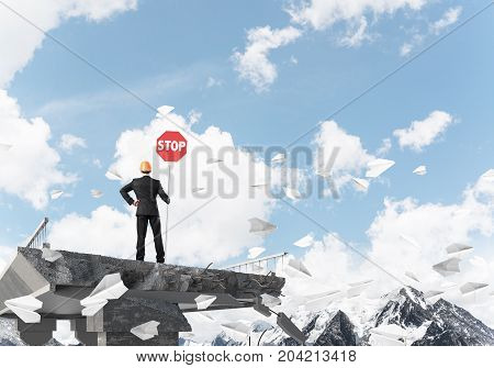 Rear view of engineer in helmet holding stop sign while standing among flying paper planes on broken bridge with skyscape on background. 3D rendering.