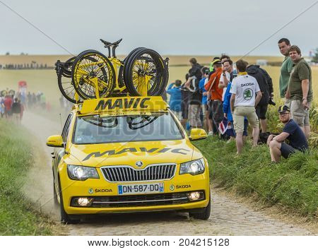 QuievyFrance - July 07 2015: Image of the technical yellow car of Mavic driving on a cobblestoned road during the stage 4 of Le Tour de France 2015 in Quievy France on 07 July2015.