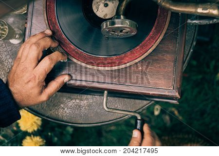 Man twists a pen on a vintage gramophone to play music, top view, toned