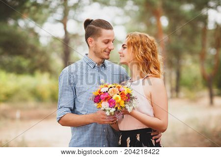 Image of love story in the forest. Beautifull couple kissing and embracing near the shore of a mountain river with decorated table. Girl smiling in the arms.