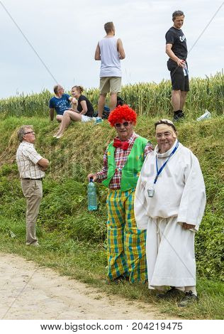 QuievyFrance - July 07 2015: Disguised spectators waiting for the cyclists on the side of the cobblestone road during the stage 4 of Le Tour de France 2015 in Quievy France on 07 July2015.