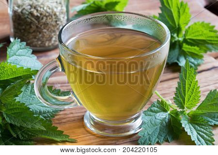 A Cup Of Nettle Tea On A Wooden Table