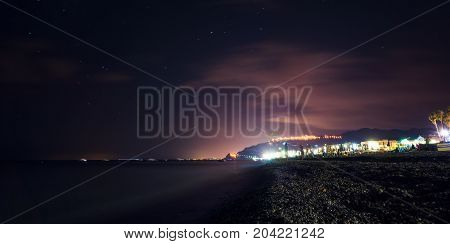 Clear summer night over the sicilian coast Furci Siculo Italy. The lights create dramatic colors over the sea
