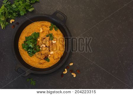 Spicy mutton  korma with cashew nuts and coriander leaves. Top view with blank space on right side