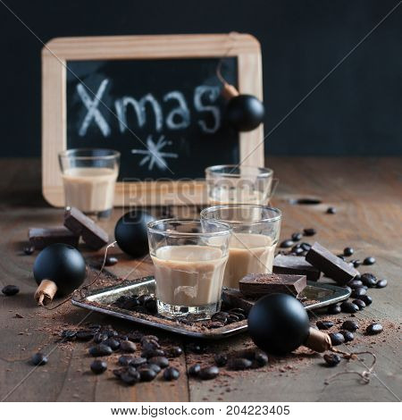 Homemade baileys or coffee liqueur in shot glasses roasted coffee beans and chocolate Christmas decoration holidays selective focus toned image square