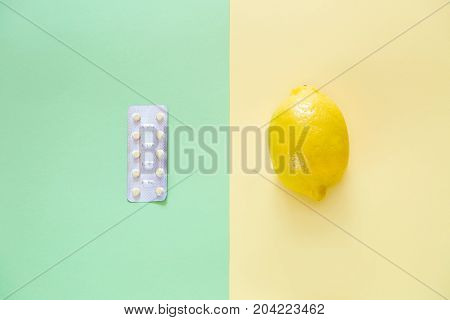 Paper background and pill on it, lemon and ginger.