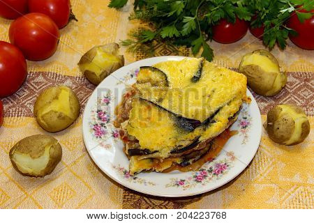 Hot Ready Moussaka Is Served On A Porcelain Plate Among Vegetables And Spicy Herbs. Fresh Vegetables