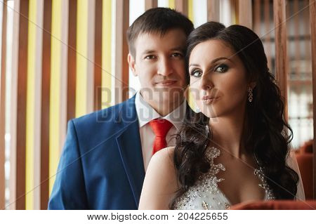 Woman In A Beautiful White Dress And A Man In A Blue Suit Hugging Near The Window. Loving And Affect