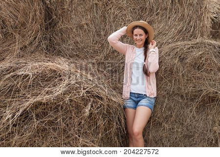 Young beautiful woman with dark hair in straw hat pink cardigan denim shorts smiling and beautifully posing against the background of large straw stacks of hay in a summer day in the village