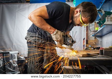 A young brunette man welder in a black T-shirt in goggles processes a metal product with a angle grinder in the garage sideways sparks