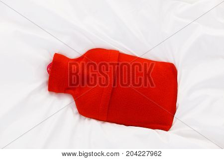 Useful things during fever concept. Warm red hot water bottle on white bedding