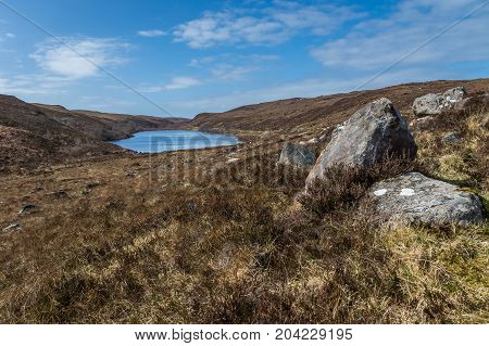 Rocks and heather with Loch na h-innse Gairbhe in the background.