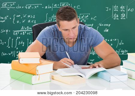 Happy Handsome Young Male University Student Studying In Front Of A Blackboard