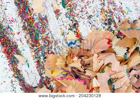 Large and small shavings from color pencils on grey background