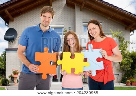 Portrait Of Happy Family Standing In Front Of Their House Holding Colorful Jigsaw Puzzles