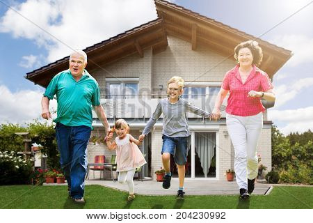 Smiling Grandparents Running With Their Grandchildren In Front Of Their House