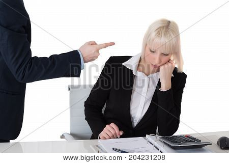 Close-up Of Businessman Scolding His Female Colleague In Office Against White Background